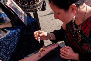 Lena sprinkles some glitter on a henna design
